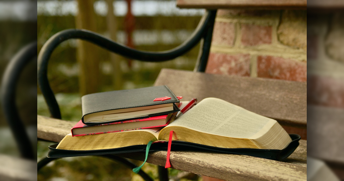 Bible and notebooks on a park bench