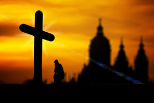 A sillhouette of a cross, a man praying and a church in the background - Photo: Pixabay / Geralt